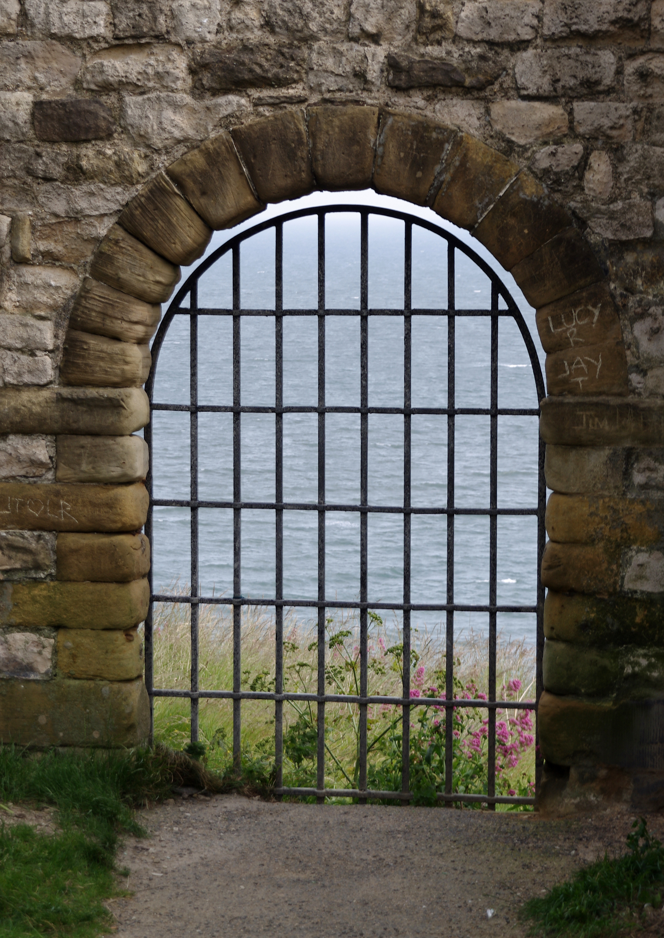 A gateway looking through the wall of Scarborough Castle onto the sea