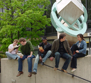 five young people sitting on stone wall in front of modern sculpture and tree