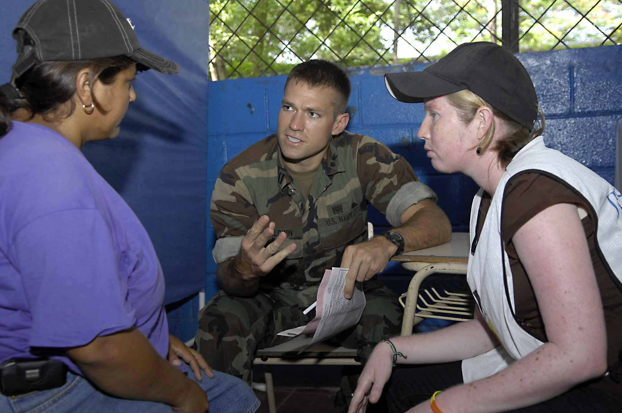 us navy 090627-f-7923s-073 navy lt. andrew baldwin and cristel martinez speak with a salvadoran woman about the problems parasites may have on a person.jpg