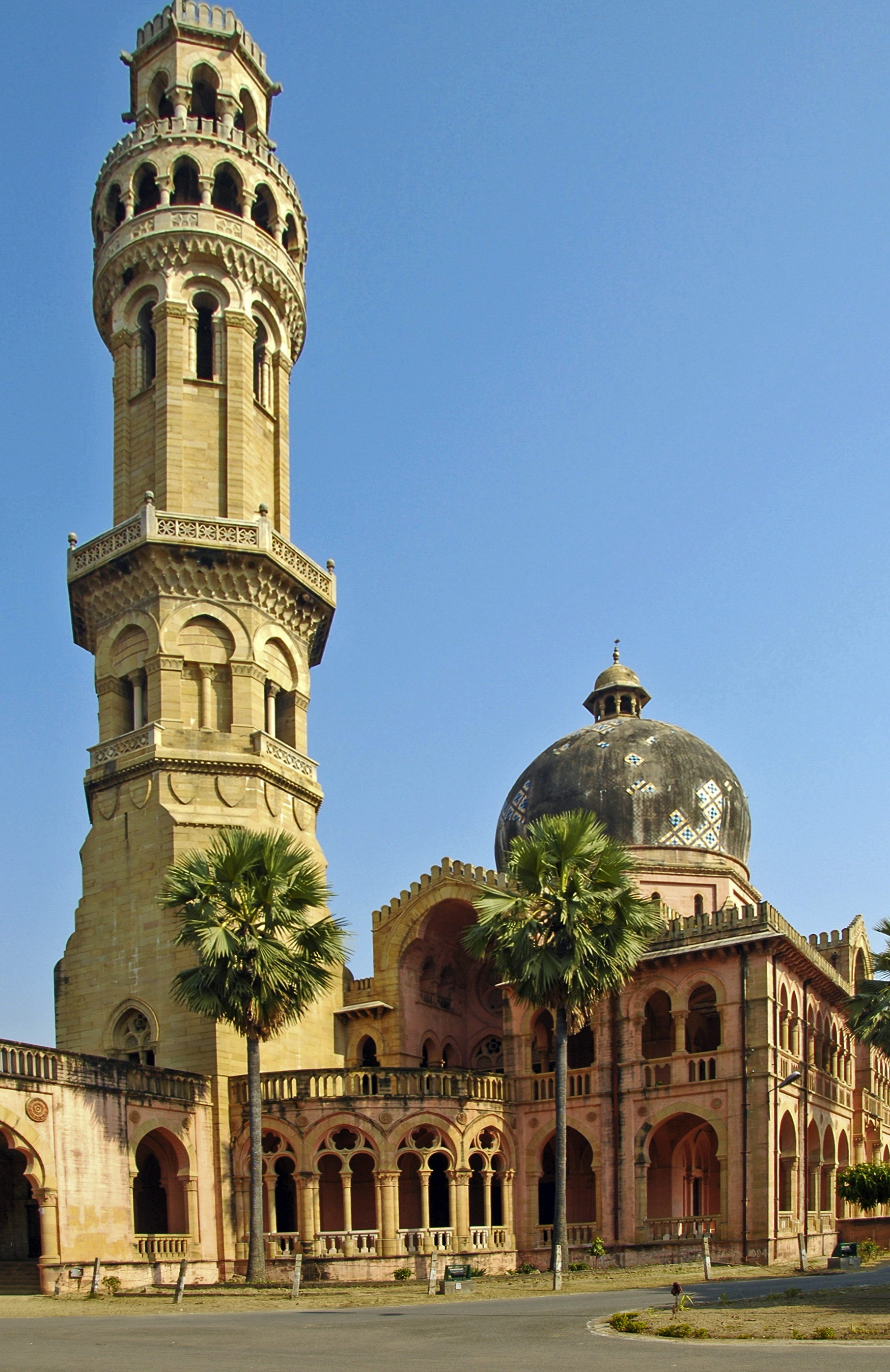 Old red building and tower, with palm trees in front