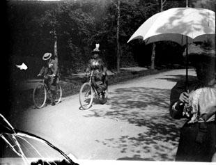 """Fonds Trutat - Photographie ancienne  Cote: TRU C 2283 Localisation: Fonds ancien (S 30)  Original non communicable  Titre: Bicyclistes et Caroline, Luchon, septembre 1895  Auteur: Trutat, Eugène Rôle de l'auteur: Photographe  Lieu de création: Bagnères-de-Luchon (Haute-Garonne) Date de création: 1895  Mesures:: 4,5 x 5,5 cm  Observations:  Note manuscrite de Trutat: """" Luchon, bicyclistes et Caroline, septembre 1895 """".  Mot(s)-clé(s):  -- Rue -- Homme -- Femme -- Bicyclette -- Surveillance -- Chemin -- Ombrelle -- Arbre -- Ombre -- Caroline  -- Bagnères-de-Luchon (Haute-Garonne) -- Bagnères-de-Luchon (Haute-Garonne; canton) -- Haute-Garonne (Midi-Pyrénées) -- Midi-Pyrénées (France)  -- 19e siècle, 4e quart  Médium: Photographies -- Négatifs sur plaque de verre -- Noir et blanc -- Scènes   numerique.bibliotheque.toulouse.fr/cgi-bin/library?c=phot...  Bibliothèque de Toulouse. Domaine public"""