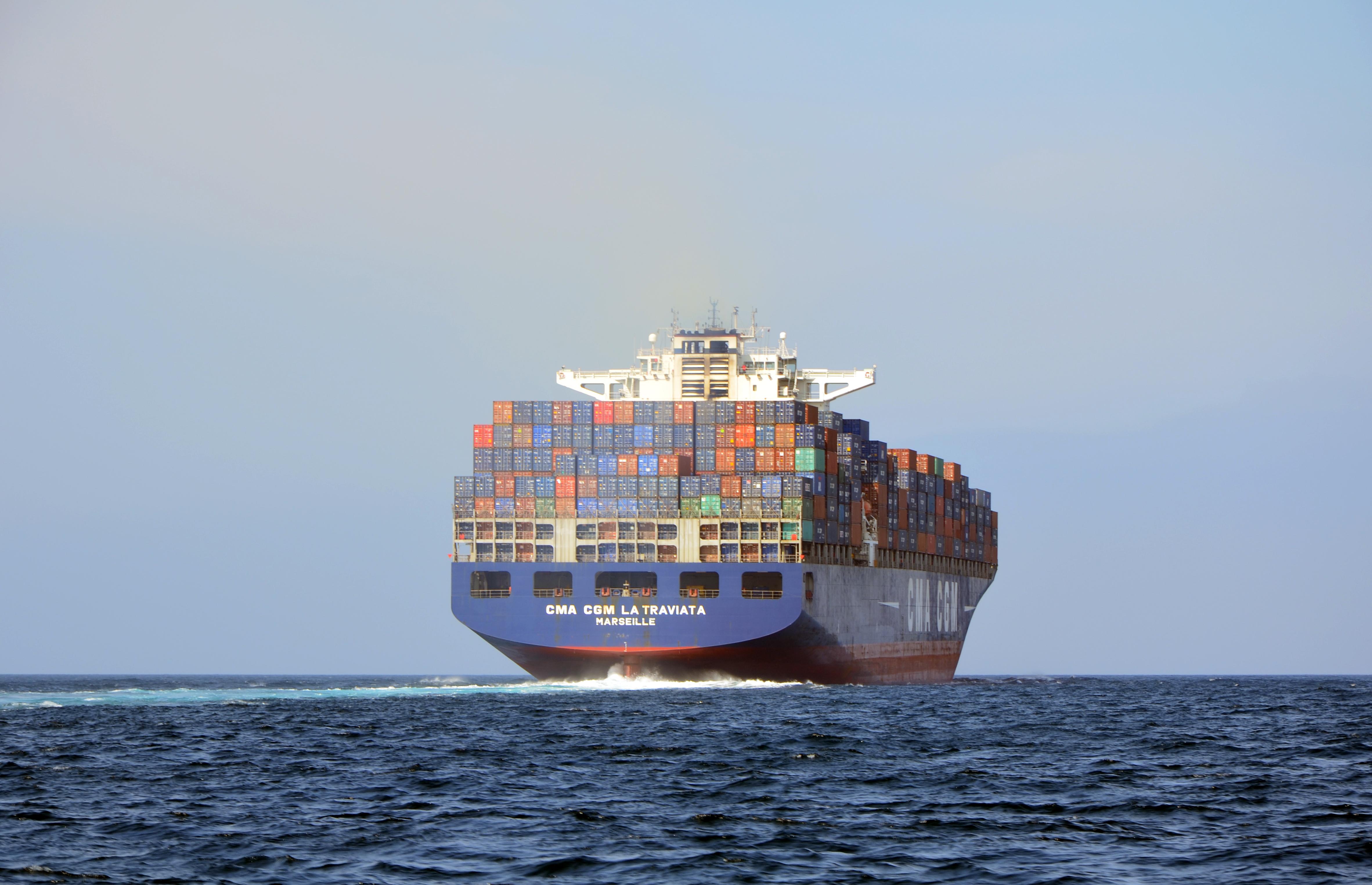 Image d'un porte-conteneurs du groupe CMA CGM qui s'en va au large, exemple de l'industrie maritime mondiale.