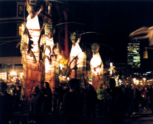 A picture from the 1998 Village Halloween Parade.  Notice the Twin Towers lit up in the background.