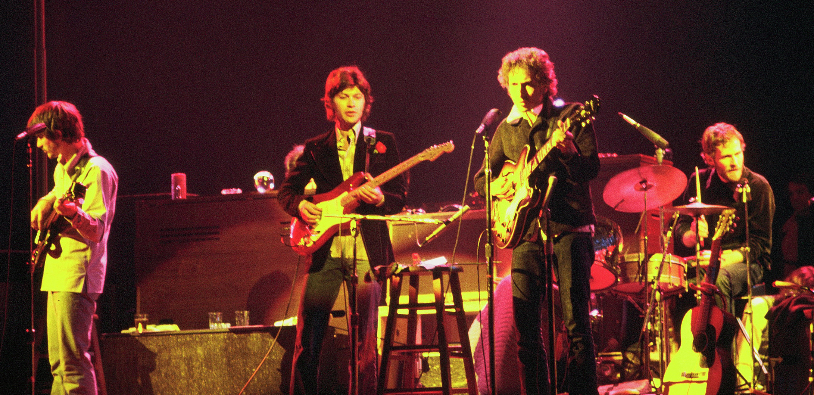 Dylan together with three musicians from The Band onstage. Dylan is third from left, wearing a black jacket and pants. He is singing and playing an electric guitar.