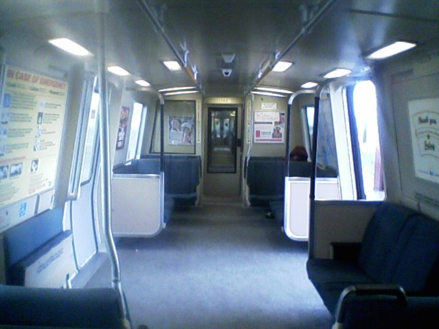 The interior of a C2 car with carpeted flooring. A flip-up seat is visible on the left.