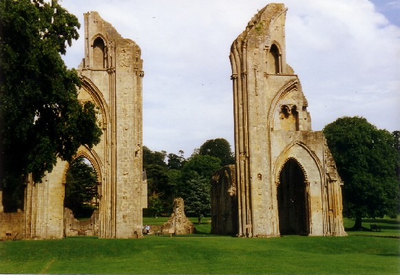 Two ruin parts of walls with arched doorways, surrounded by grass and trees.