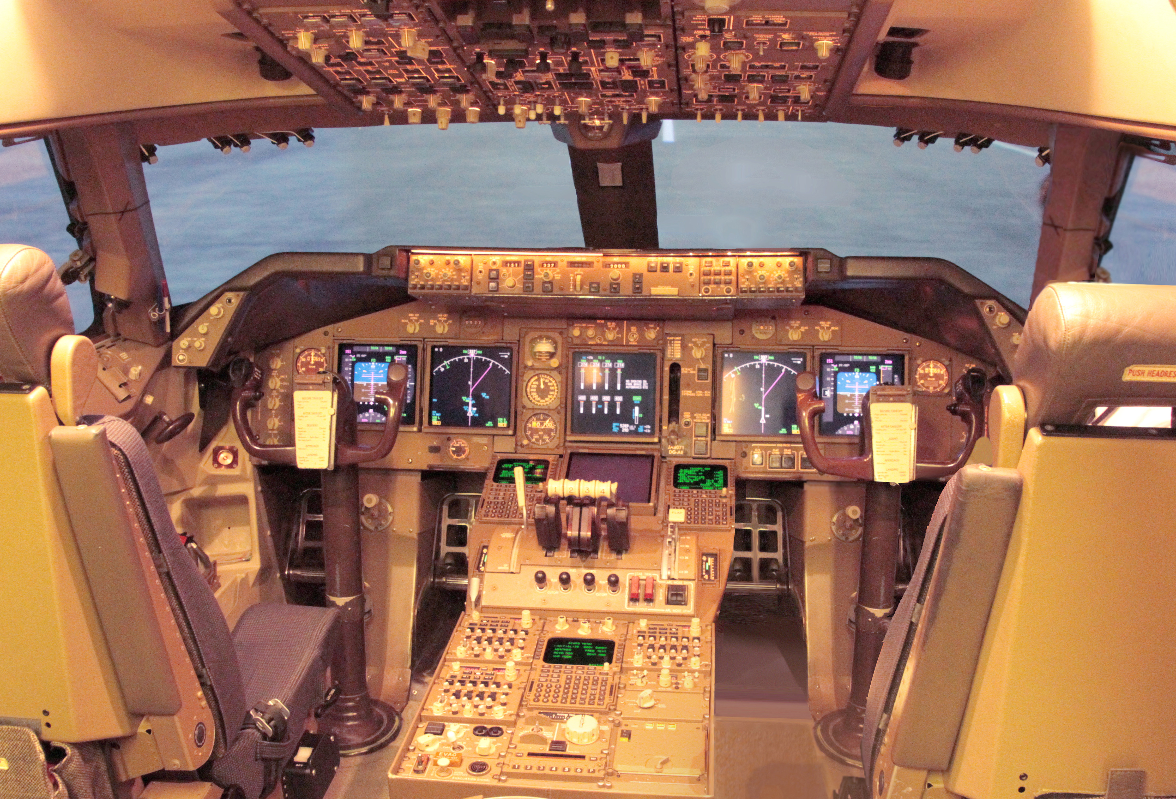 Cockpit of modern jet airliner, showcasing digital displays and instruments. Light enters through the windshield.