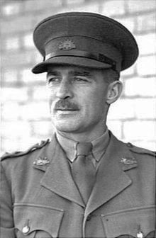 Head-and-shoulders portrait of moustachioed man in military uniform with peaked cap