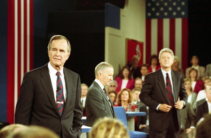 George H. W. Bush, Ross Perot, and Bill Clinton stand on a stage during the second presidential debate on 15 October 1992.