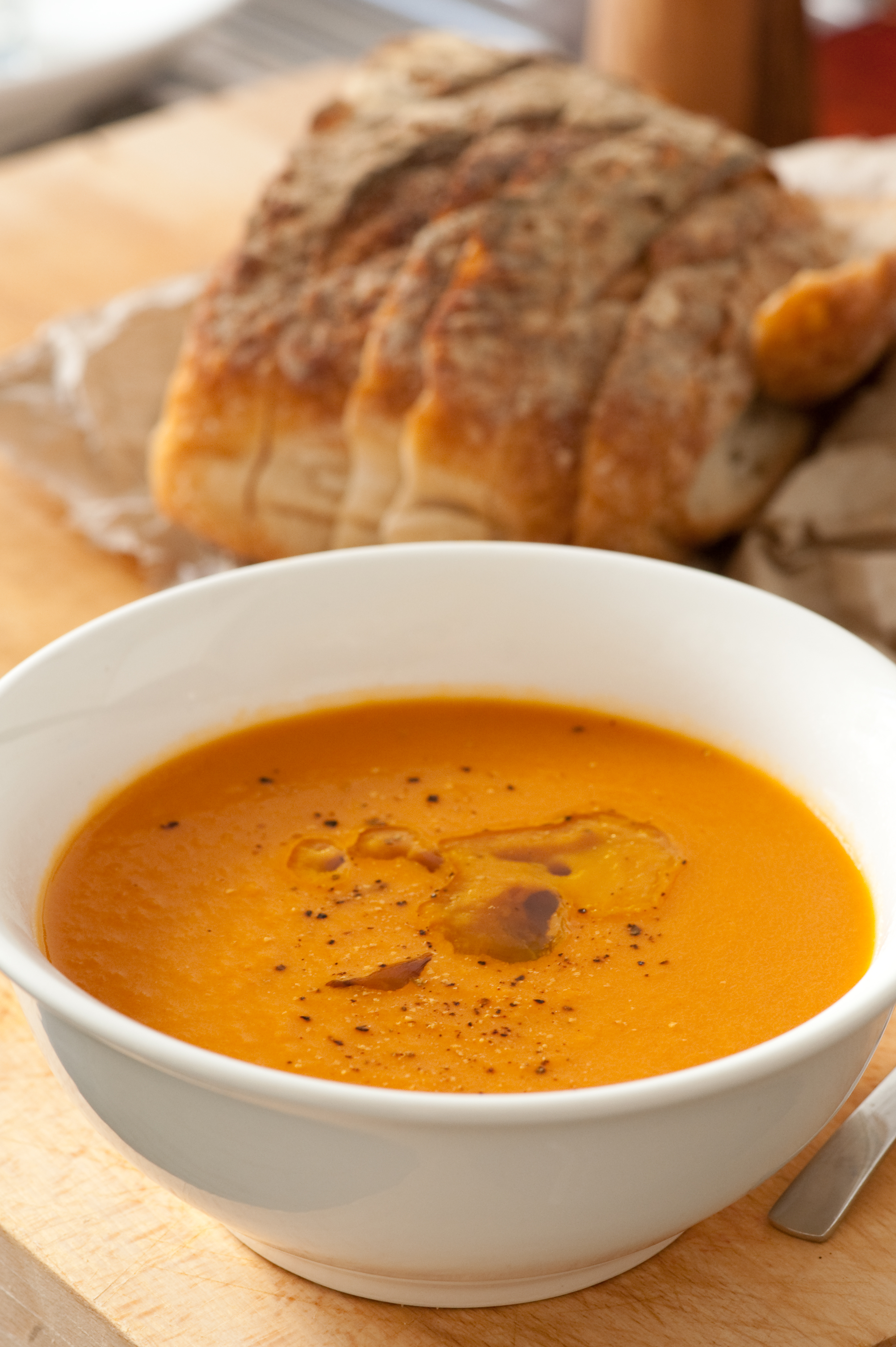 A bowl of bright-orange, beta-carotene rich carrot soup with crusty bread