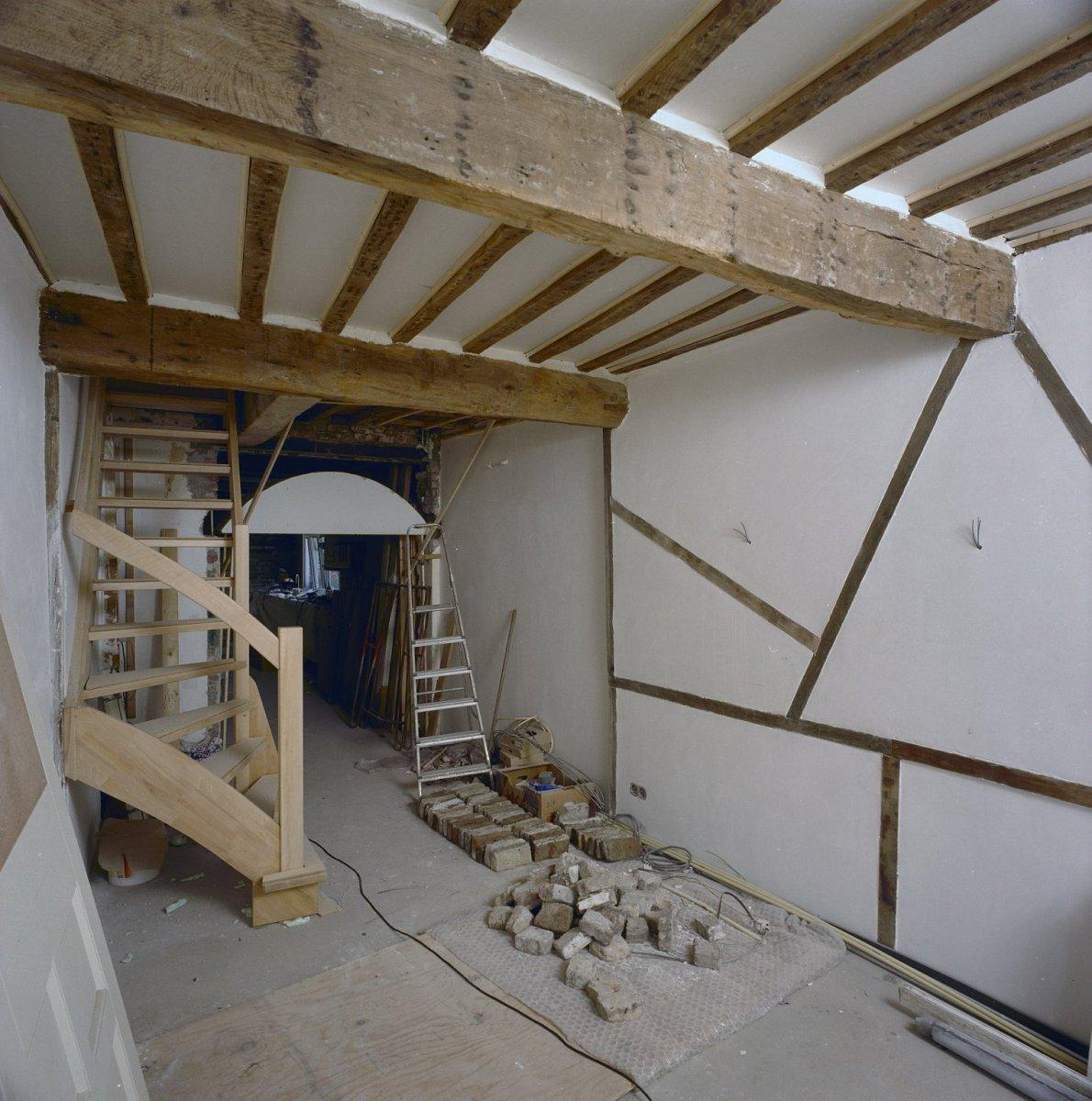 File interieur woonkamer met vakwerkwand en open trap Trap in woonkamer
