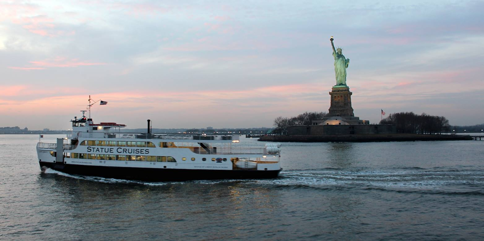 Statue Cruises Ferry Boat in New York Harbor in front of the Statue of Liberty