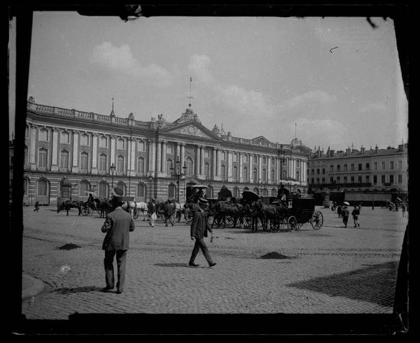 Hôtel de ville, place du Capitole. Juillet 1905.  Vue générale de la place.  Façade de l'hôtel de ville; façades sud de la place; à gauche passants; à droite voitures à attelage et cochers.