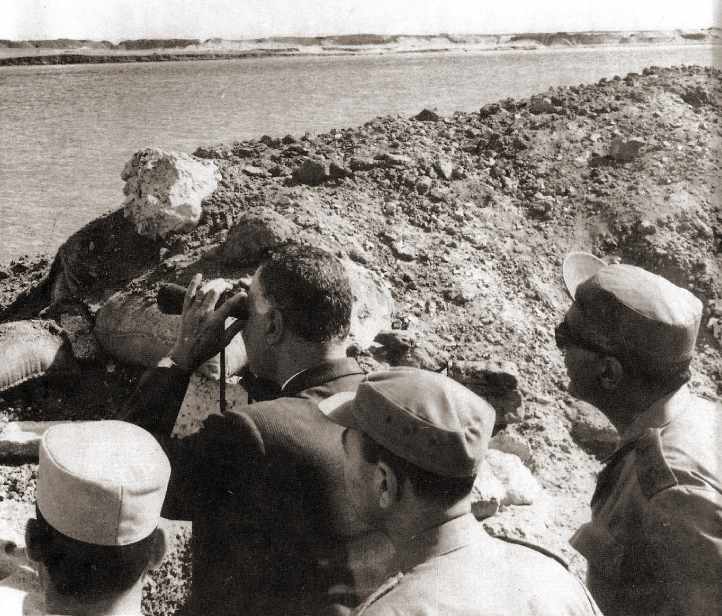 A man wearing suit peering out across a body of water with binoculars from an opening in dirt mound. Behind him are three men in military uniform