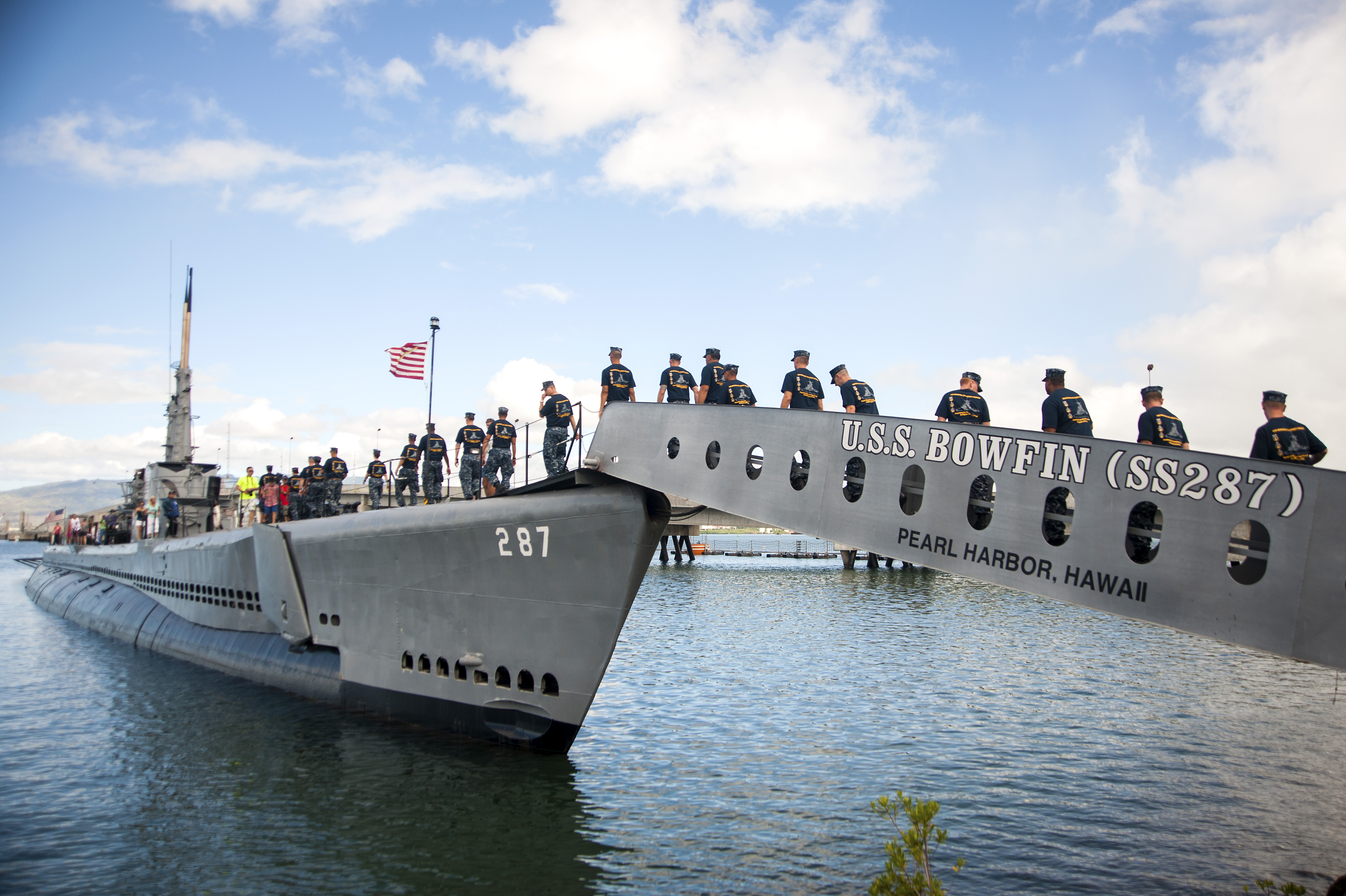 uss bowfin a gray ww2 ship docked at pearl harbor, with a line of sailors walking on deck