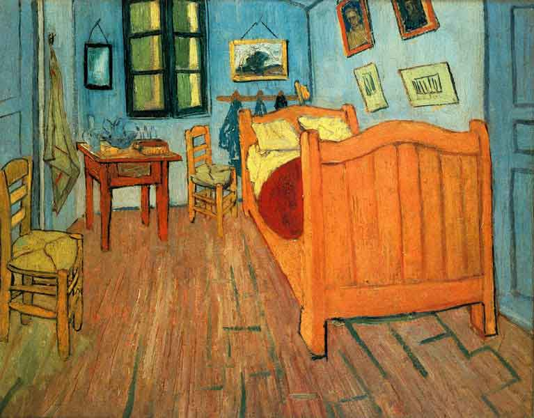 A narrow bedroom with wooden floor, green walls, a large bed to the right, a 2 straw chairs to the left, and a small table, a mirror and a shuttered window on the back wall. Hanging over the bed are several small pictures
