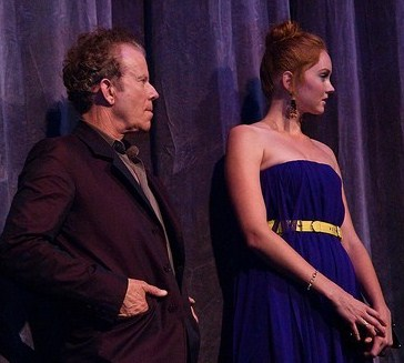 A red-haired woman in a long blue dress (Lily Cole) standing next to a shorter, Caucasian man with salt and pepper hair, wearing a dark suit
