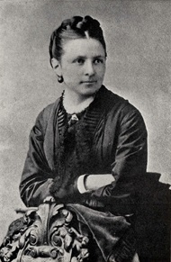 A woman with tight hair and a dark shawl top sits with her arms crossed, facing to the viewer's right with her body turned to the viewer's left
