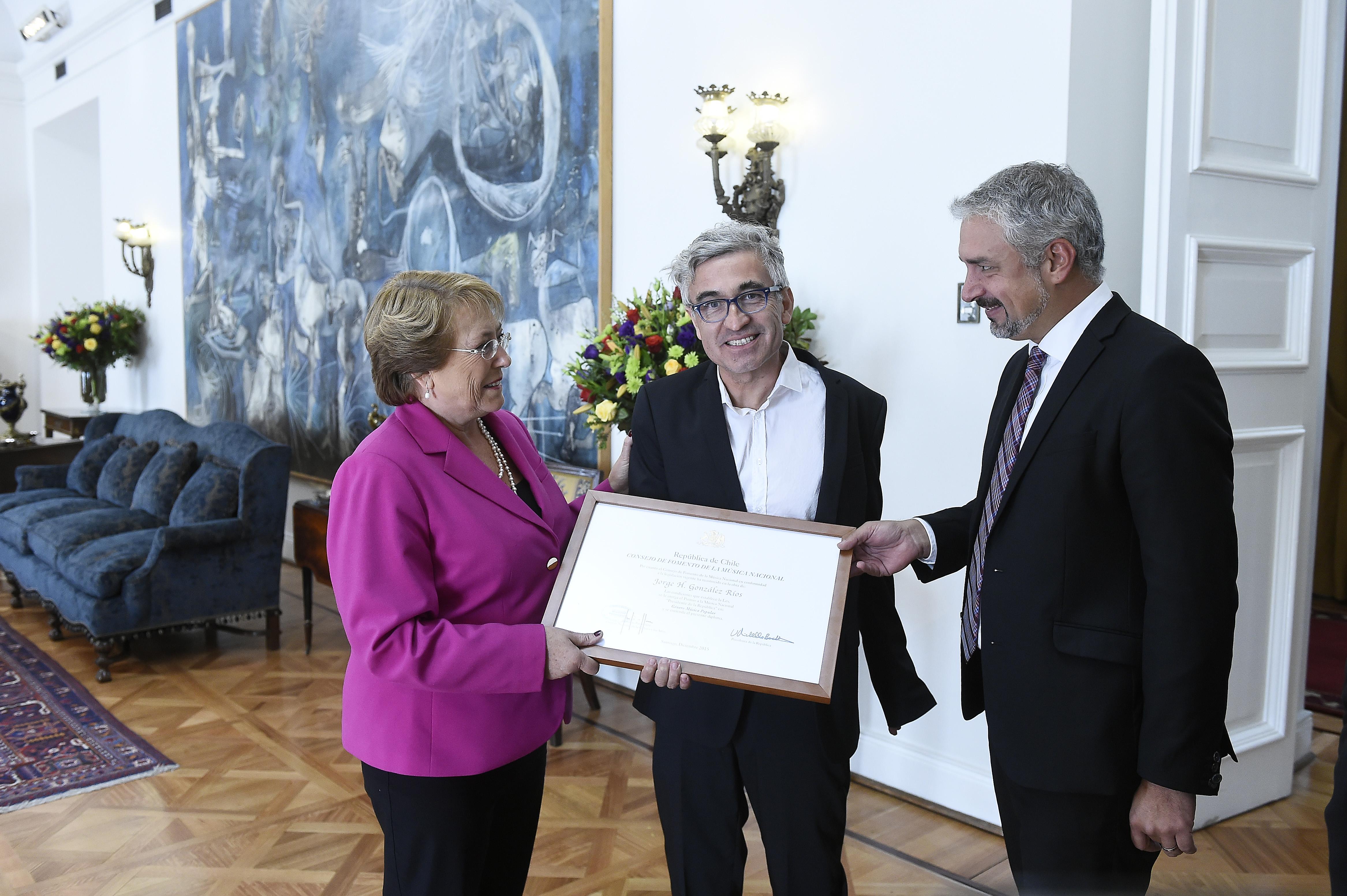 Jorge González (al centro) recibe de manos de la Presidenta Michelle Bachelet el Premio a la Música Nacional Presidente de la República, categoría Música Popular (2016).