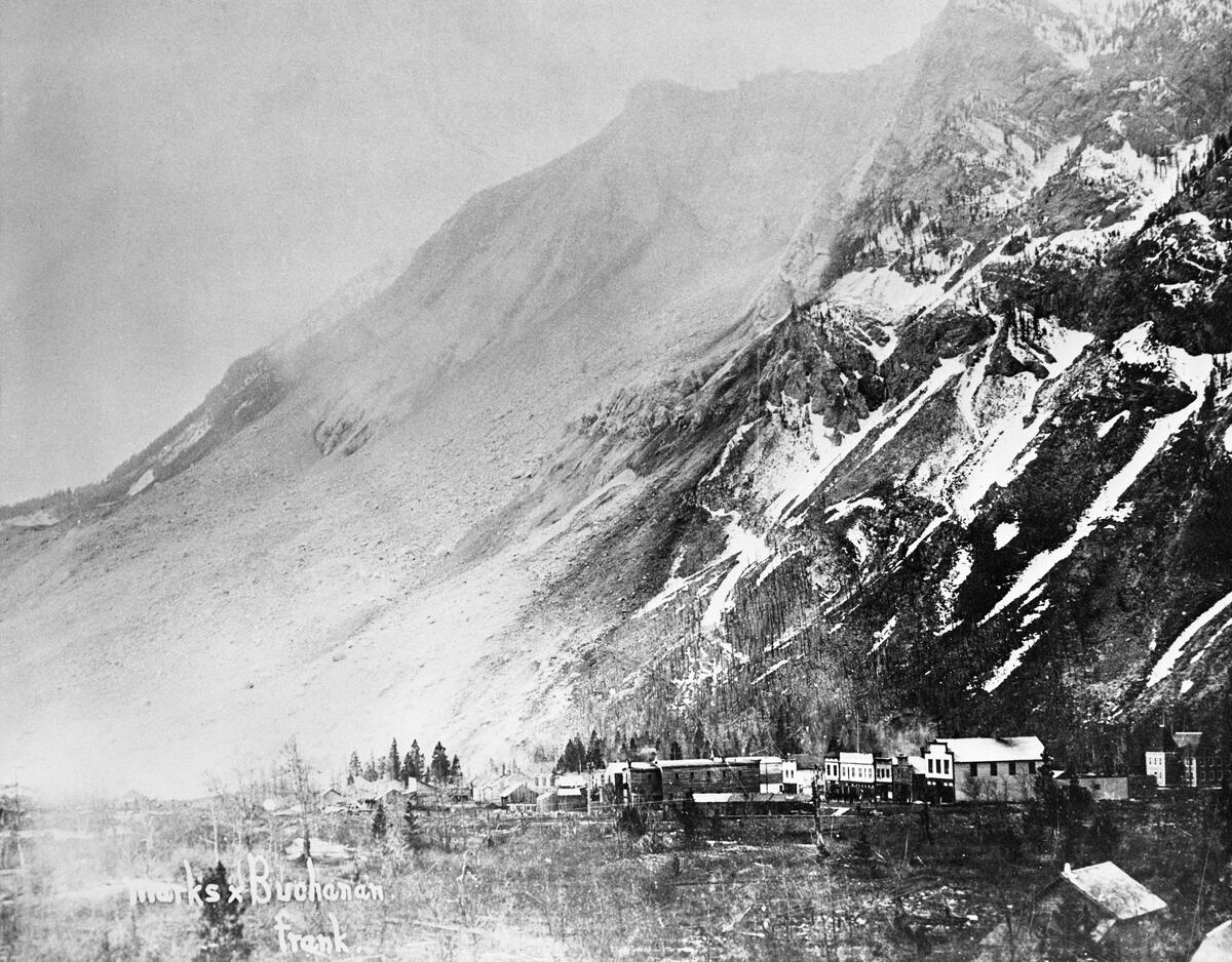 A small town shown at the base of a mountain. The mountain's face stands barren following a large rockslide and a light cloud of dust is visible in the air.