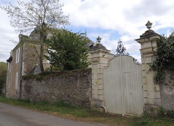 Château de la Noue, portail avec 2 gros piliers à droite et mur d'enceinte, batiment et toitures derrière un bosquet au dessus de ce mur à gauche