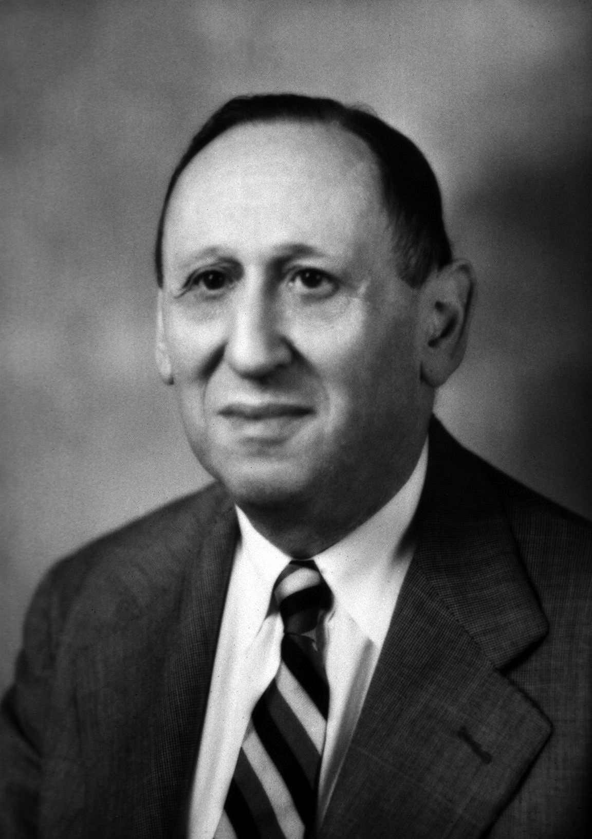 Head and shoulders of a man in his early 60s in coat and tie, facing slightly to his right. He is balding and has a serious but slightly smiling expression.