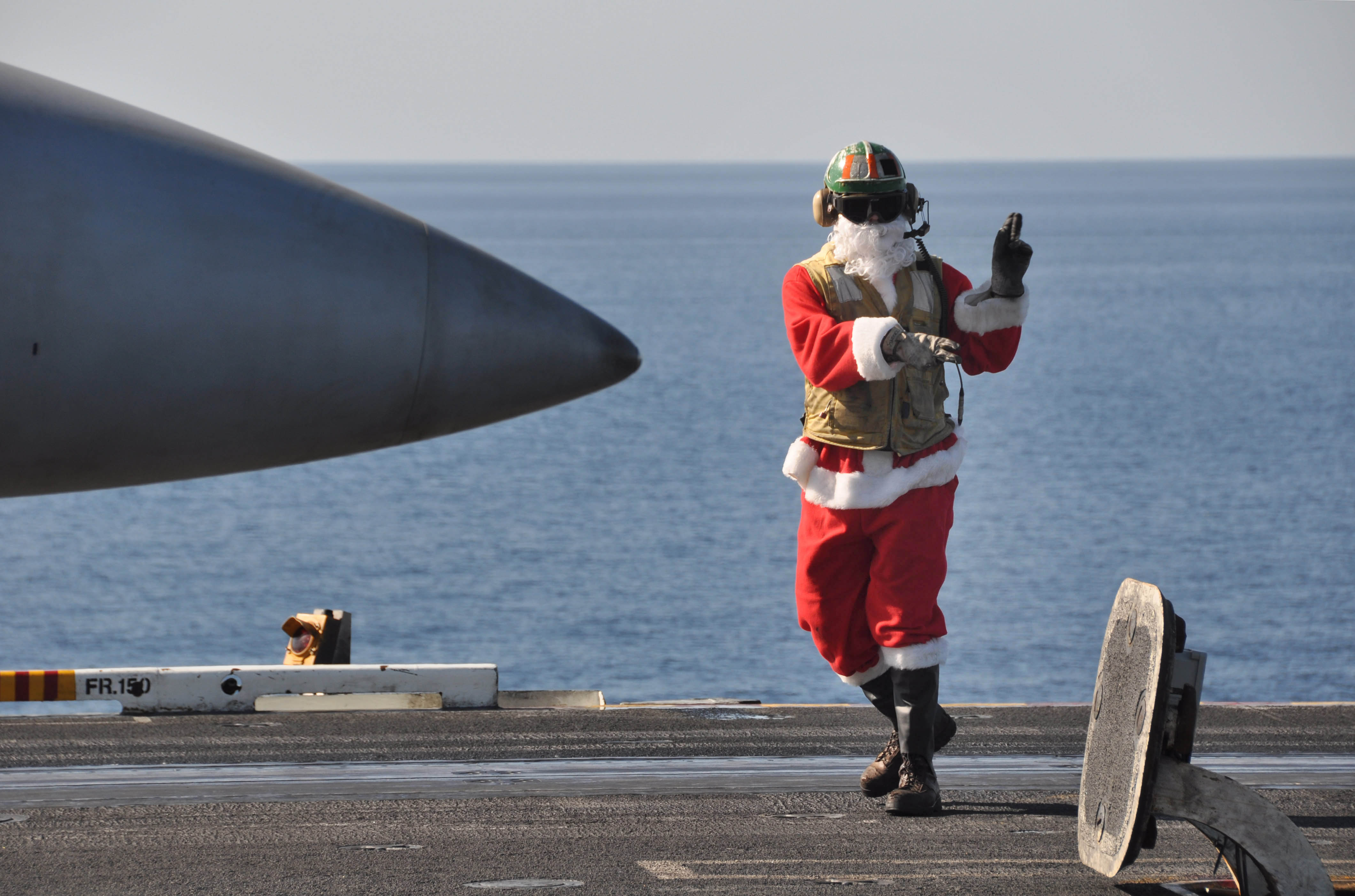 Merry Christmas US_Navy_091225-N-8421M-103_t._Jon_Sunderland_dresses_in_a_Santa_suite_while_directing_aircraft_operations_aboard_the_aircraft_carrier_USS_Nimitz_(CVN_68)_Christmas_Day