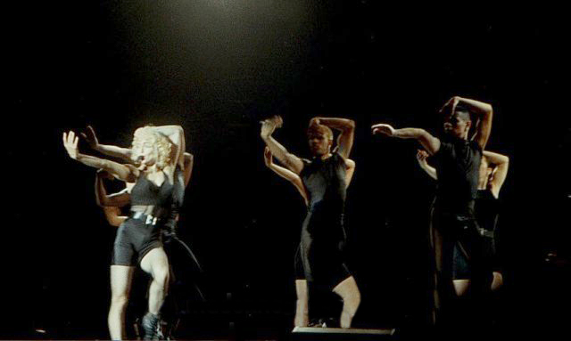 A young blond woman dancing with a group of dancers. They are all wearing black outfits.