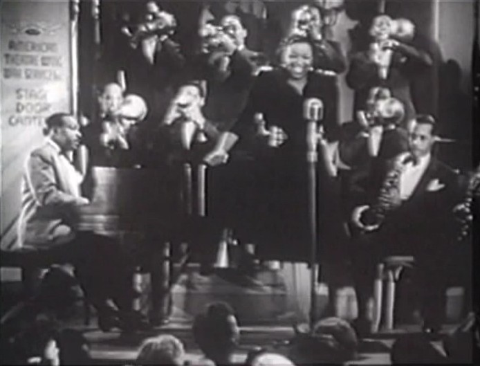 Screenshot of the bandleader Count Basie with his band, and featured singer Ethel Waters from the film ''Stage Door Canteen'' (1943)