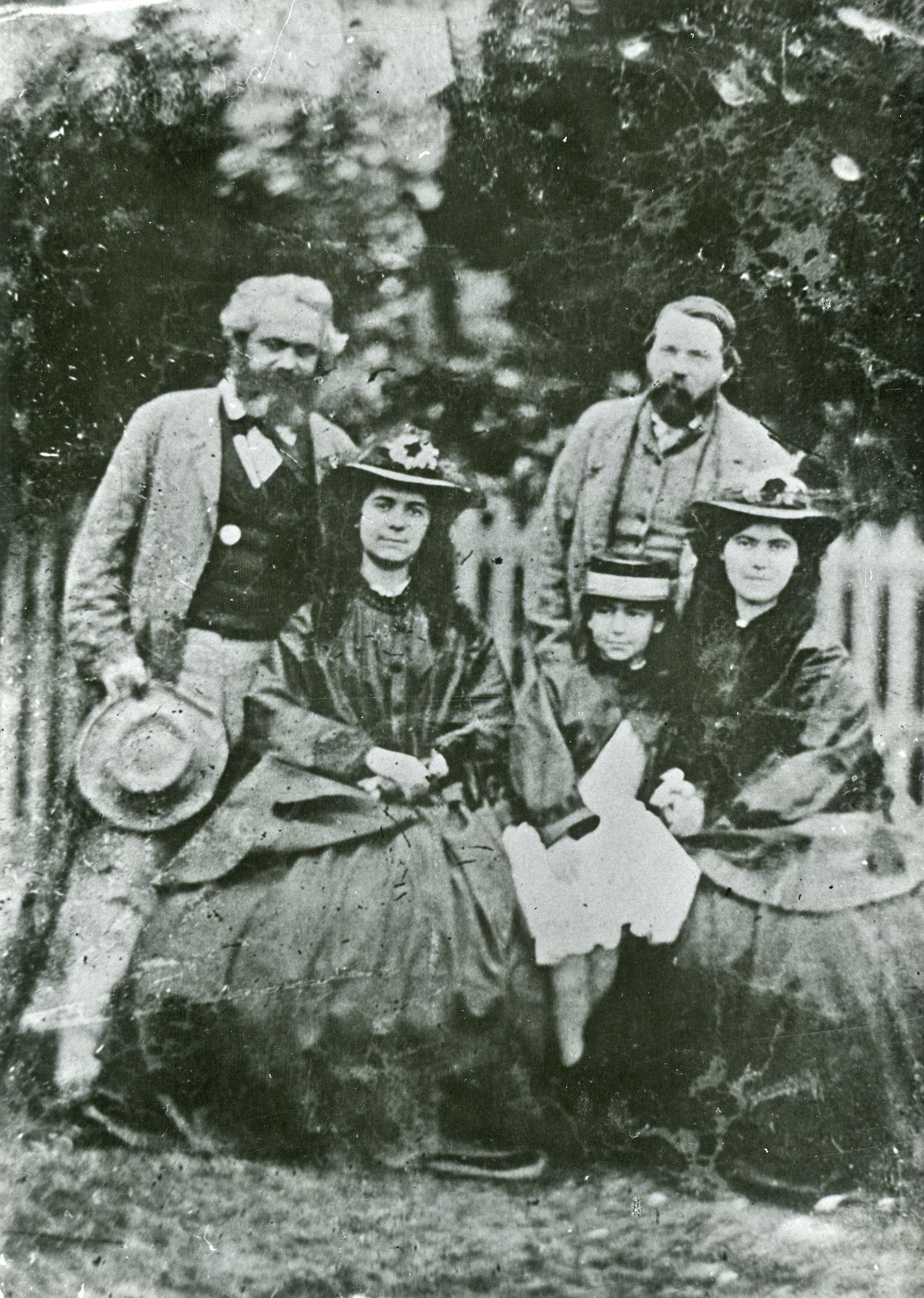 Friedrich Engels, Karl Marx y las hijas de éste: Jenny Caroline (1844–1883), Jenny Julia Eleanor (1855–1898), y Jenny Laura (1845–1911). La imagen está tomada aproximadamente en 1864.
