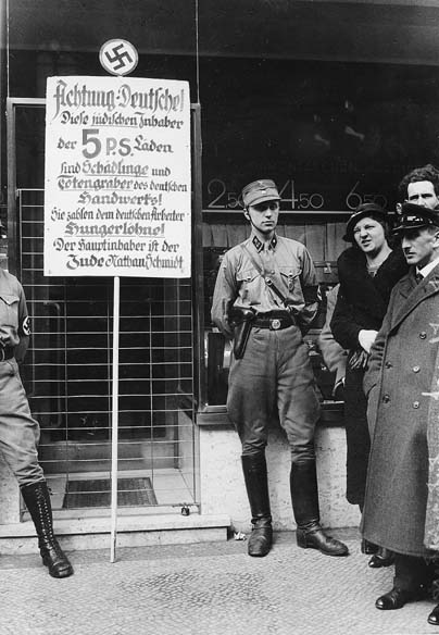 "Boycott of Jewish Shops April 1, 1933: Members of the SA in front of a Jewish shop during the boycott of Jews in Nazi-Germany on April 1, 1933. The sign says: ""Germans, Attention! This shop is owned by Jews. Jews damage the German economy and pay their German employees starvation wages. The main owner is the Jew Nathan Schmidt."""
