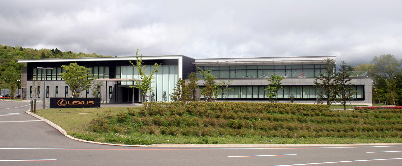 alt=Rectangular windowed building, with landscaping and a sign in front labeled 'Lexus'.