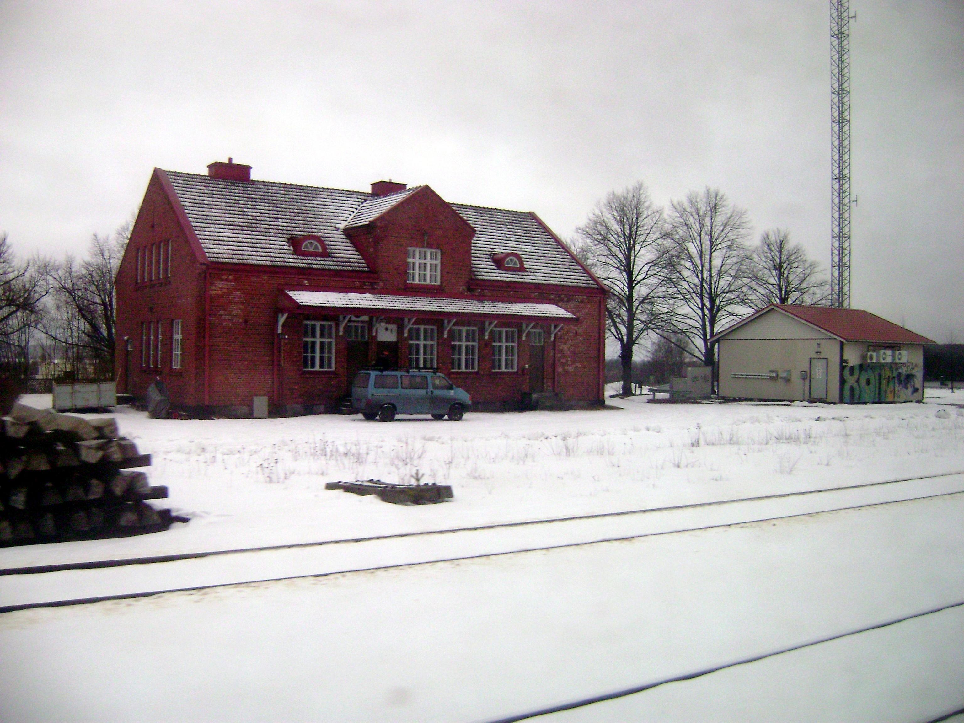 Talvisessa kuvassa on tiilestä rakennettu Lielahden asema junaradan puolelta. Talon edessä on sininen pakettiauto. Vasemmalla on kasa kiskojen alle tulevia pölkkyjä. Kuvassa kiskot menevät edessä poikittain.