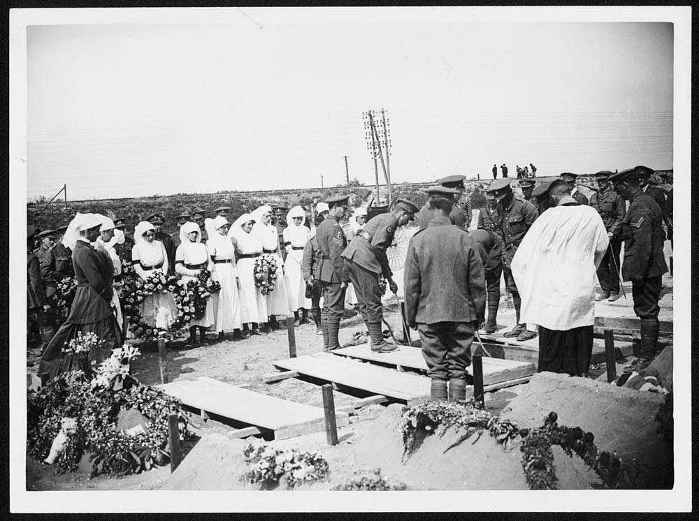 Funeral of a Red Cross nurse, Western Front, during World War I. Soldiers lowering the coffin of a Red Cross nurse into a grave. Other nurses stand around holding wreaths and a bugler is waiting at the head of the grave. This is one of three photographs of the funeral which are attributed to Tom Aitken.In spite of the huge numbers of men killed during the war, these photographs suggest that there was still an element of shock at the death of a woman, especially a nurse. [Original reads:  'OFFICIAL PHOTOGRAPH TAKEN ON THE BRITISH WESTERN FRONT IN FRANCE. Funeral of British Red Cross Nurse who was killed during the German Air Raid on Red Cross Hospital. Lowering the coffin.'] http://digital.nls.uk/74549104
