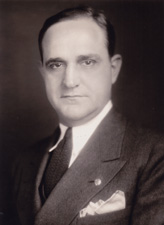 A half-length portrait of a man wearing a suit with a smirk on his face and a slight purple hue about him