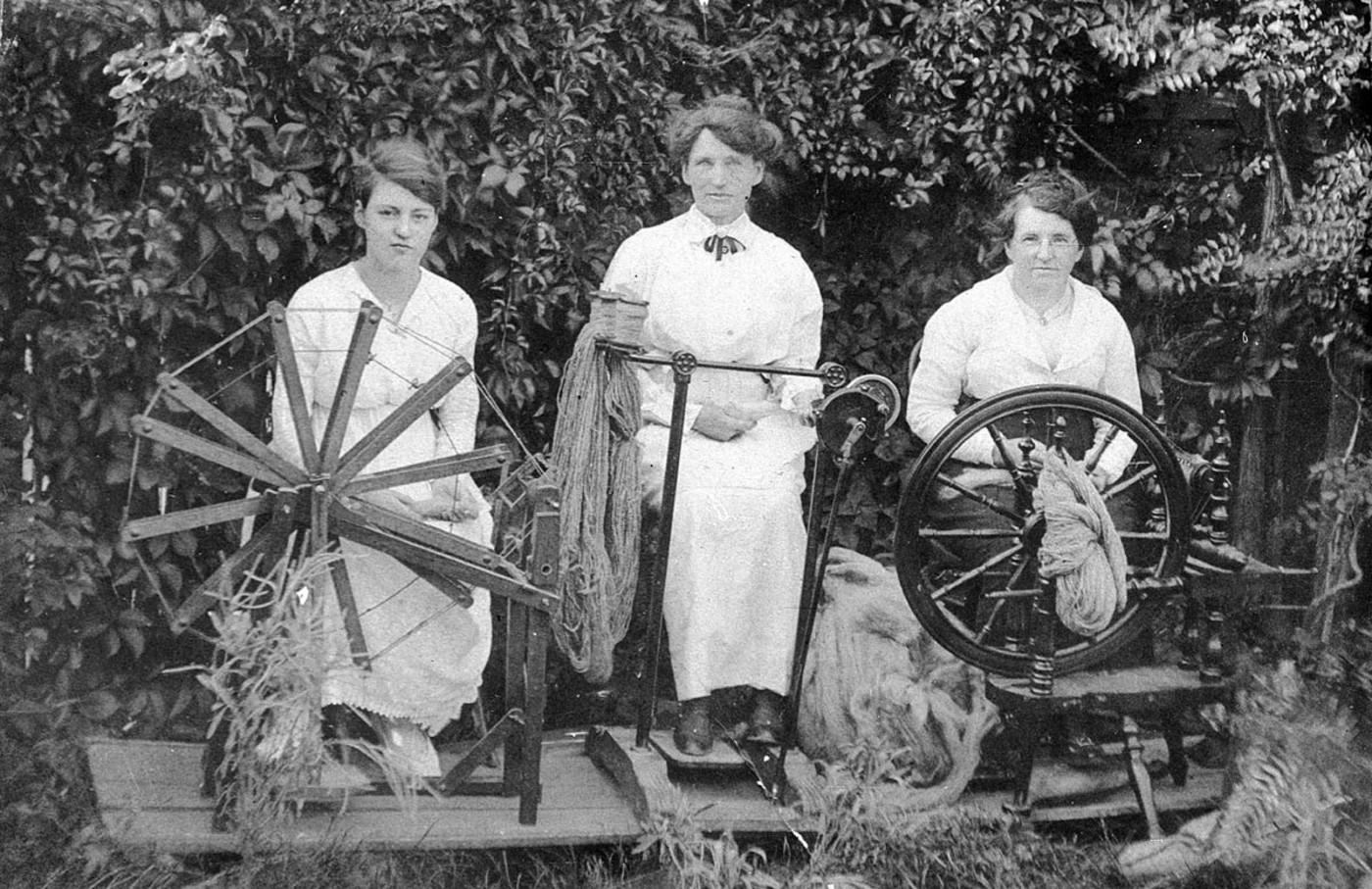 Three women spinning wool.