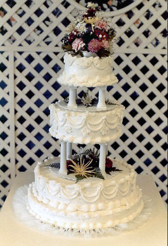 Wedding cake with pillars and floral decoration - Wedding Ceremony Description