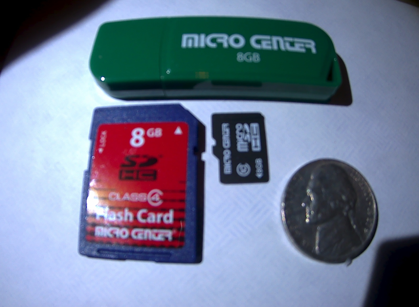 Comparison of three flash media from Micro Center computer store: thumb drive, SD and Micro-SD cards, all having capacity of 8 gigabytes, next to a U.S. nickel