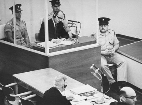 Adolf Eichmann takes notes during his trial. Photo by Israel Government Press Office. Public Domain.