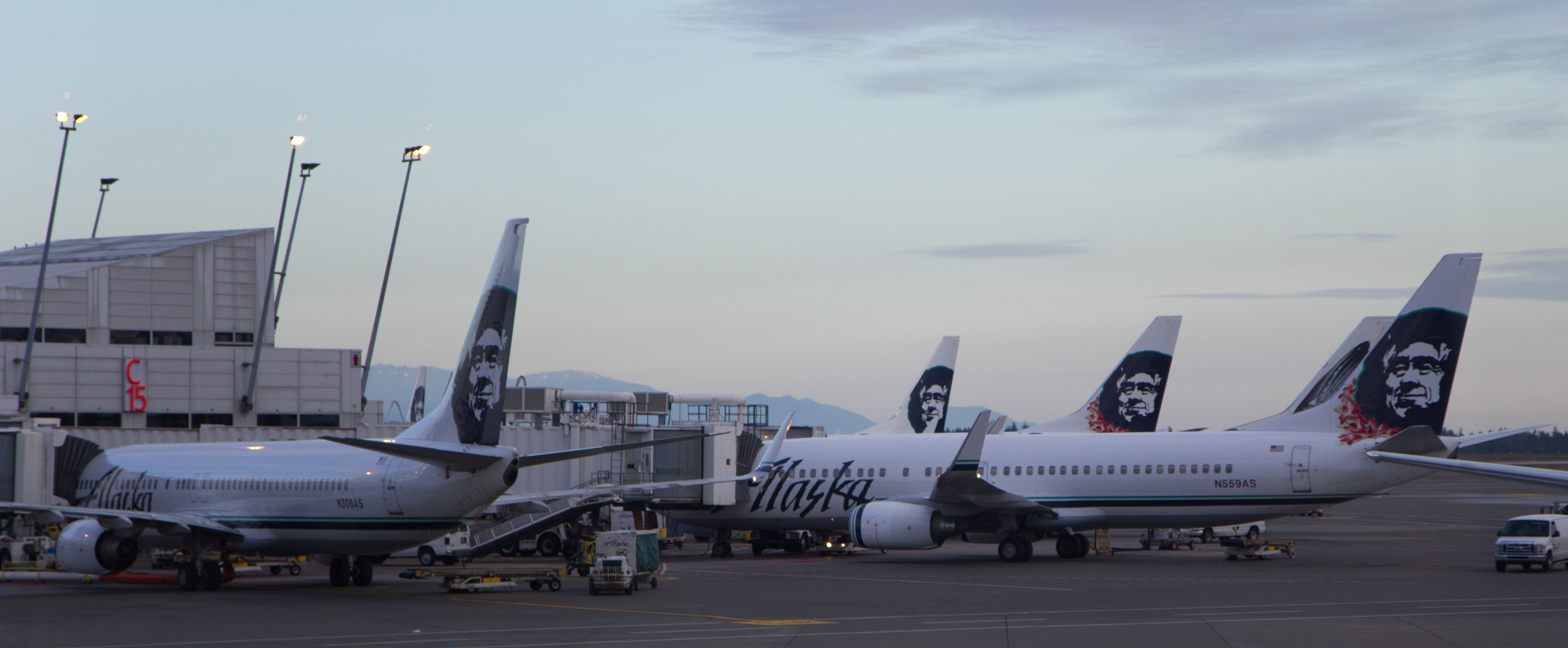 Early morning photo showing Alaska Airlines aircraft parked at an airport terminal, with jetways connected to the planes. Five aircraft can be seen in the photo.