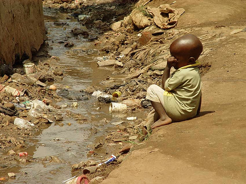 Child in slum in Kampala (Uganda) next to open sewage (3110617133).jpg