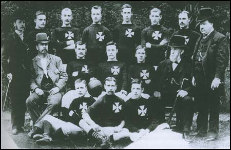 Fifteen men posing across three rows. Eleven of the men are wearing a football kit with a Maltese Cross on the breast. The other four are wearing suits and top hats.