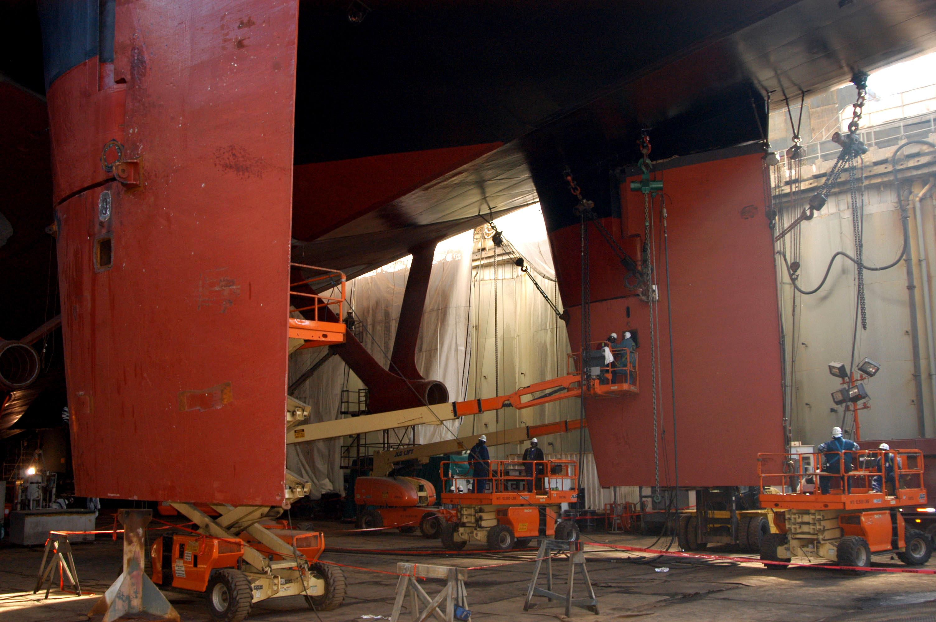 Workers from Northrop Grumman Newport News shipyard install