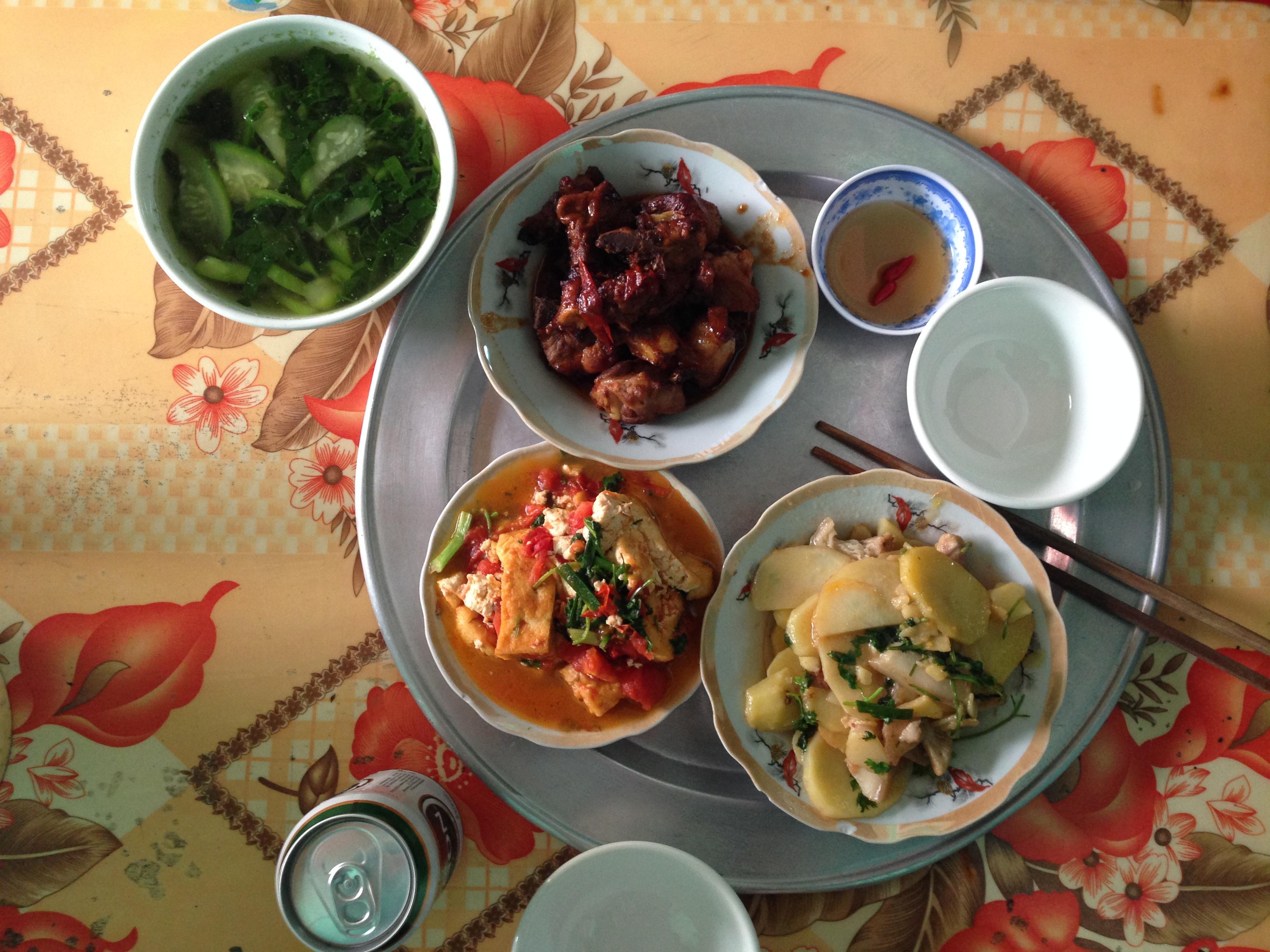 Một bữa cơm của gia đình Việt Nam hiện đại dọn trên mâm tròn với nguyên liệu đa dạng: sườn, đậu phụ, khoai tây, cà chua, bầu, mồng tơi và nước mắm ớt