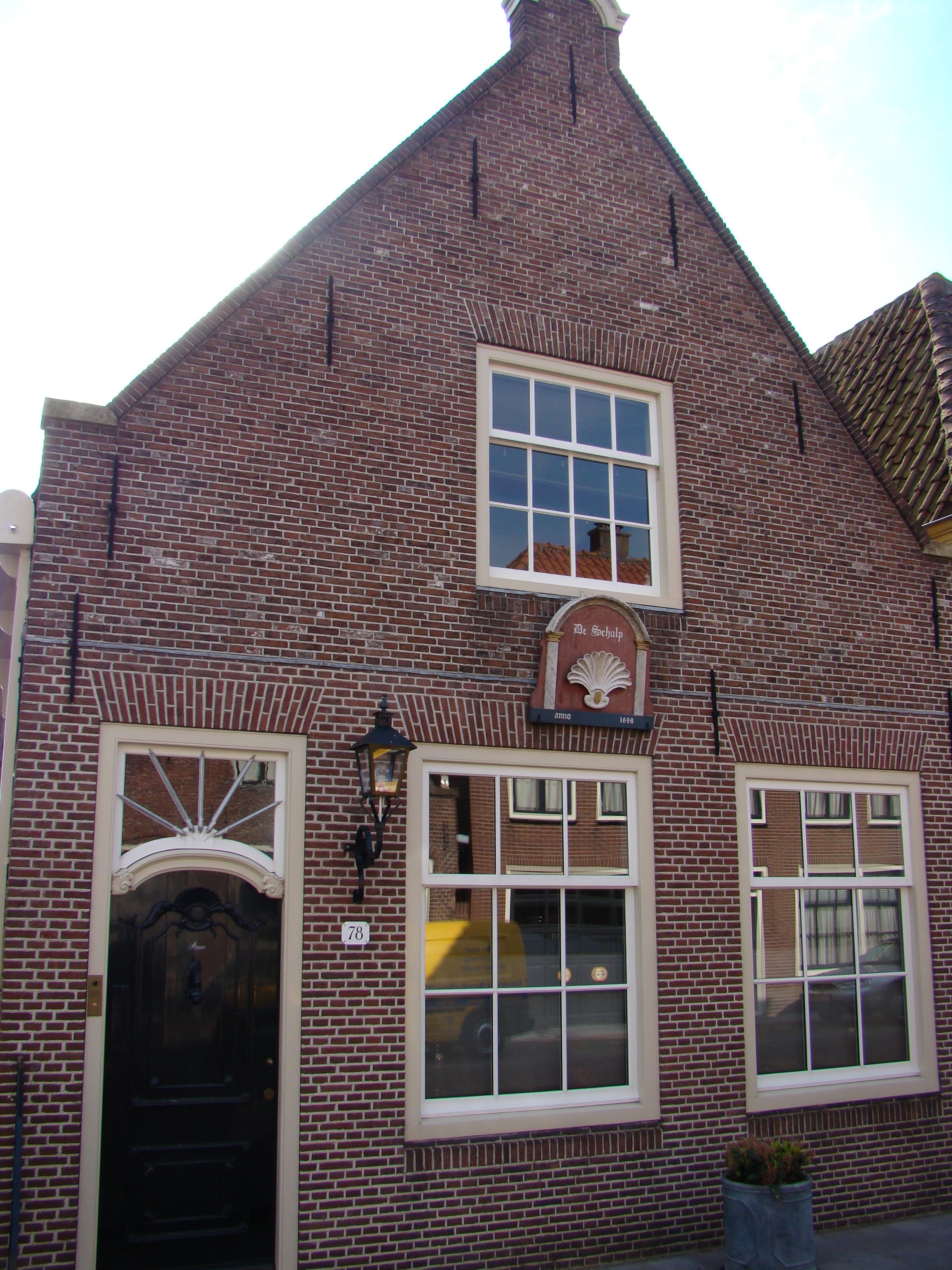 Huis met eenvoudige gevel voorzien van een gebogen topafdekking in monnickendam monument - Huis gevel ...