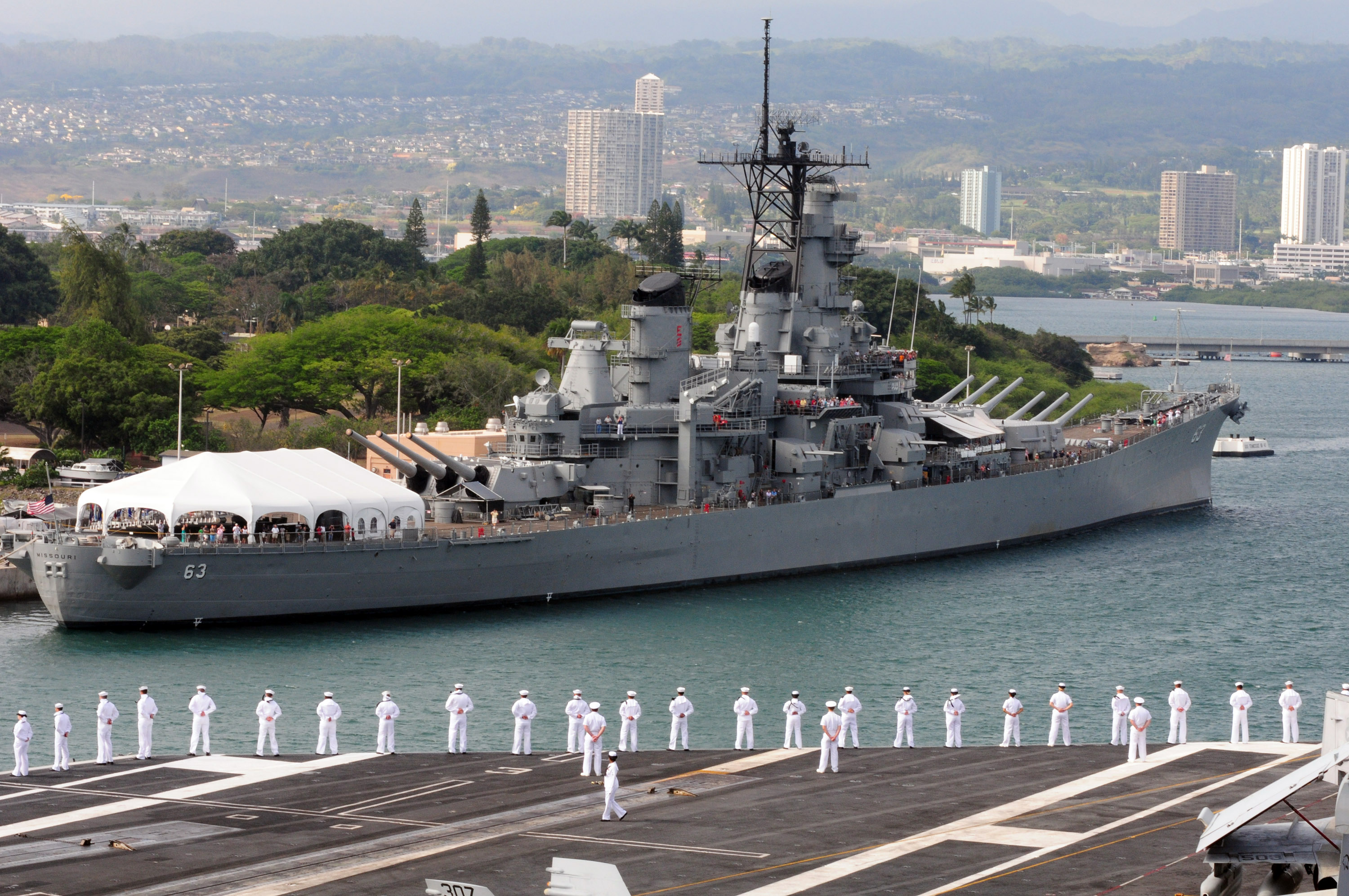 uss missouri docked at pearl harbor, dark green trees in the background, line of sailors in white uniform salute from the dock
