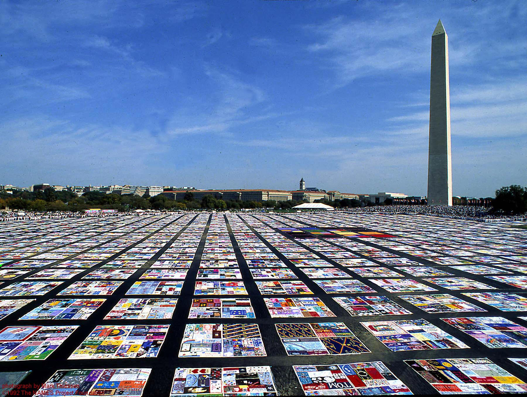 Photograph of the AIDS Memorial Quilt laid out beneath the Washington Monument.