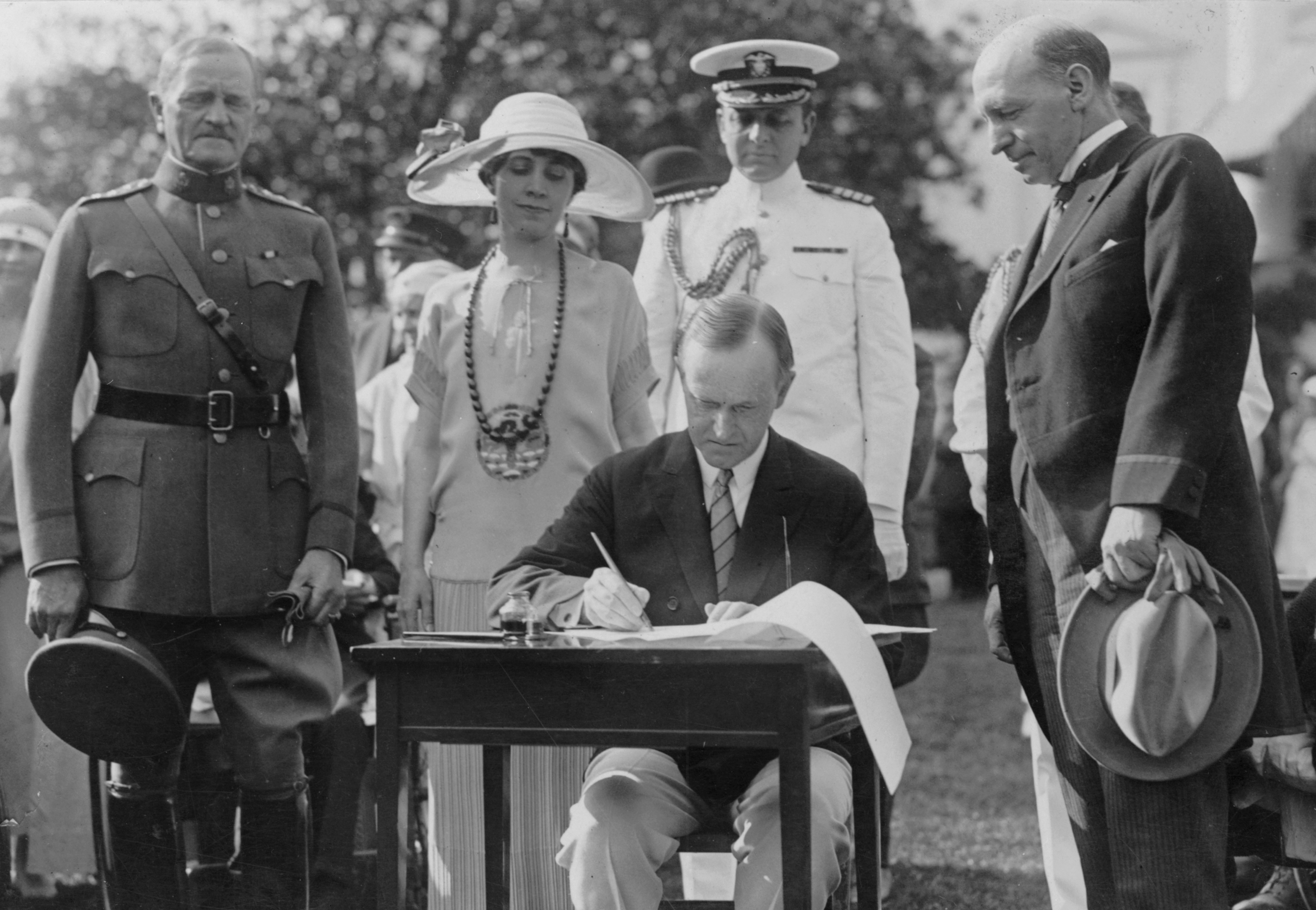 President Coolidge signing appropriation bills for the Veterans Bureau on the South Lawn during the garden party for wounded veterans, June 5, 1924. General John J. Pershing is at left. The man at right, looking on, appears to be Veterans Bureau Director Frank T. Hines. CalvinCoolidgeimmigration3.jpg