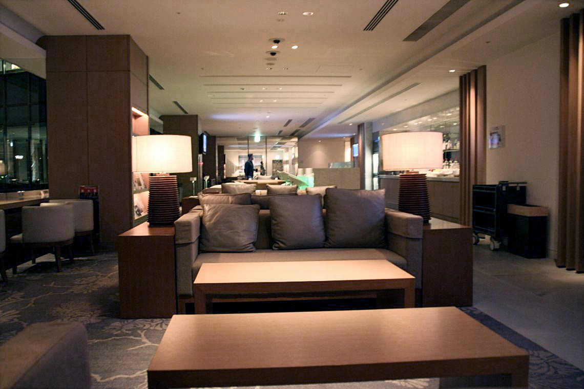 A three-seater couch with two coffee tables in the front and two side tables on both side, all in neutral brown colour