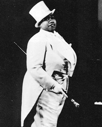 A black-and-white photo of Bentley in a white tux with tails, holding a cane and wearing a tophat